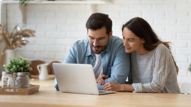 Happy young mixed race married spouse making purchases online. Pleasant family couple sitting at big wooden table in modern kitchen, looking at laptop screen. Happy young mixed race married spouse web surfing, making purchases online or booking flight tickets. husband stock pictures, royalty-free photos & images