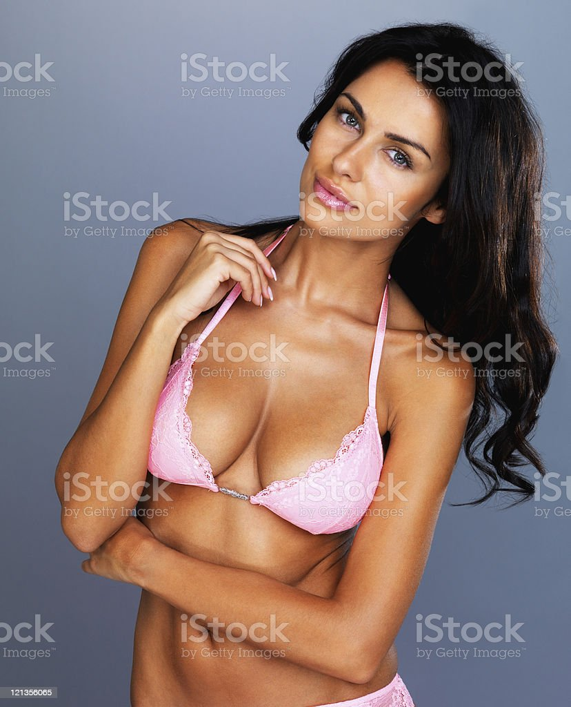 Happy young model in pink bikini against grey background stock photo