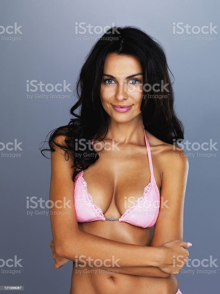 Happy young model in pink bikini against grey background royalty-free stock photo
