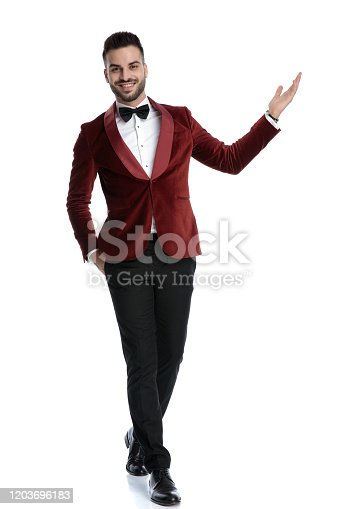 happy young model in tuxedo smiling and presenting to side, walking isolated on white background, full body