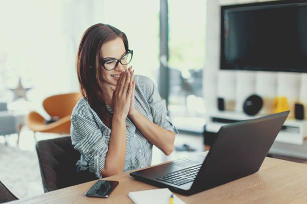 gelukkig jonge moderne zakenvrouw lezen goed nieuws op laptop - aanbrengen stockfoto's en -beelden