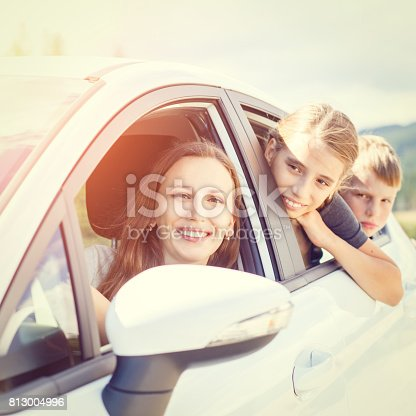 istock Happy young mom and her children sitting in a car 813004996