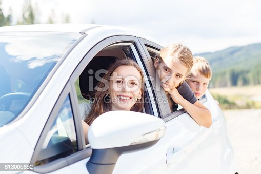 istock Happy young mom and her children sitting in a car 813005652