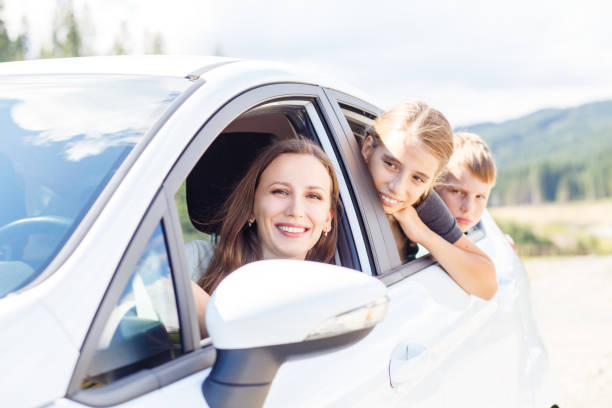 Happy young mom and her children sitting in a car Happy young woman and her children sitting in a car and look out from windows. Family travel background image sergionicr stock pictures, royalty-free photos & images