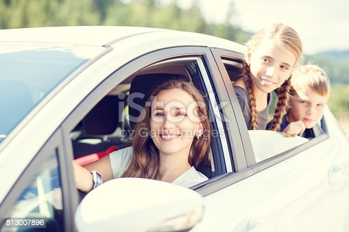 658502852 istock photo Happy young mom and her children sitting in a car 813007896