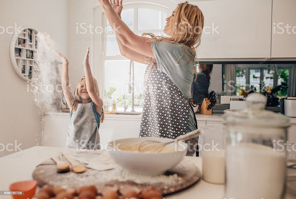 Happy young mother and daughter having fun in kitchen stock photo