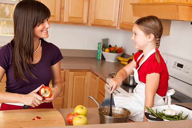 glückliche junge mutter und ihre tochter kochen zusammen in der küche - peeling zu hause machen stock-fotos und bilder