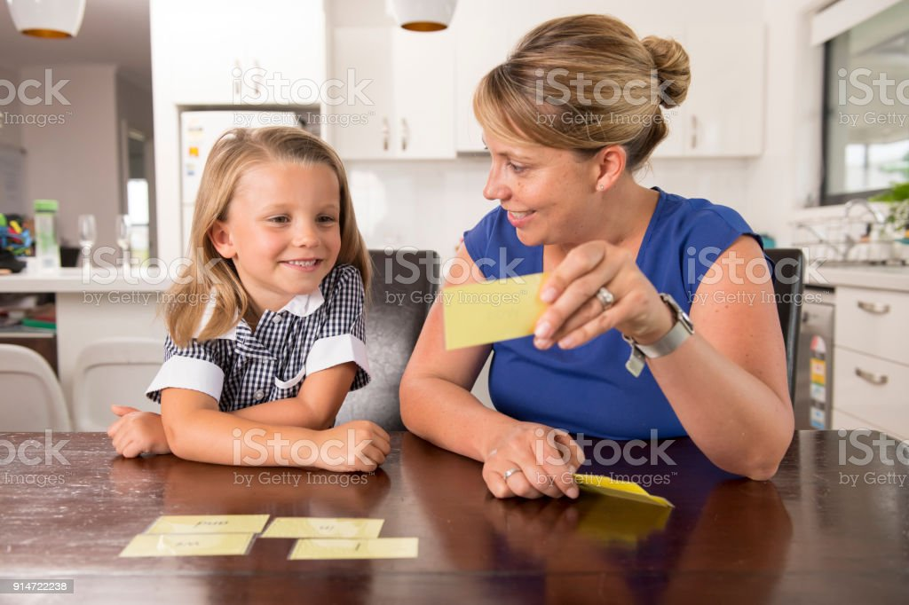 happy young mother and her sweet and beautiful little daughter playing card game at home kitchen smiling and having fun together in education and family lifestyle concept stock photo