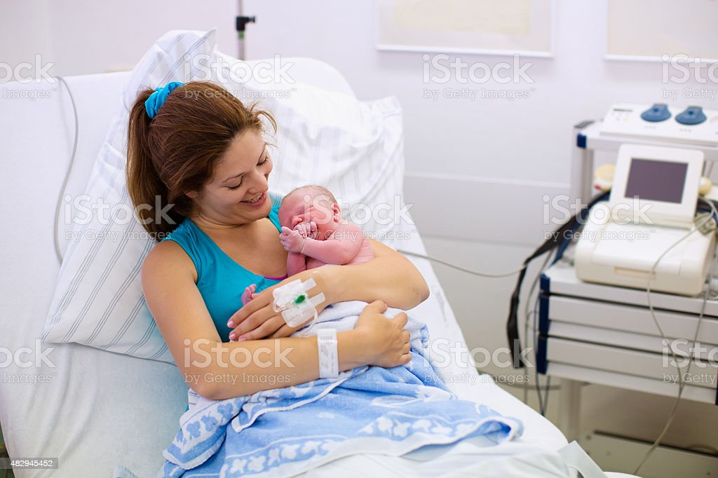 Happy young mother giving birth to a baby stock photo