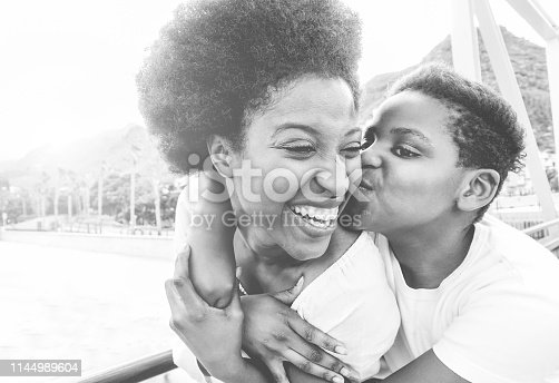 Happy young mother having fun with her child in summer day - Son kissing his mum outdoor - Family lifestyle, motherhood, love and tender moments concept - Focus on woman face - Black and white filter