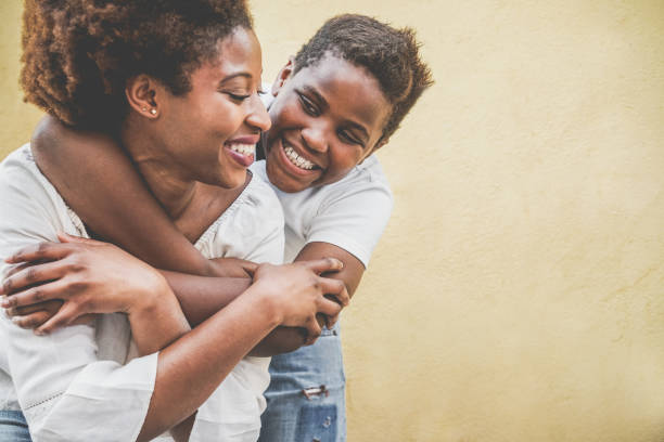 Happy young mother having fun with her child - Son hugging his mum outdoor - Family lifestyle, motherhood, love and tender moments concept - Focus on kid face stock photo