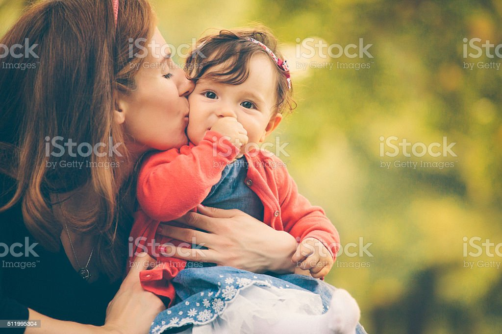 Happy young mother kissing her baby girl stock photo