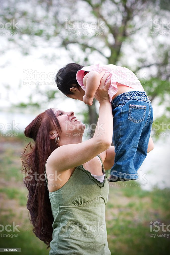 Happy Young Mother Lifting Baby Outdoors in Nature royalty-free stock photo