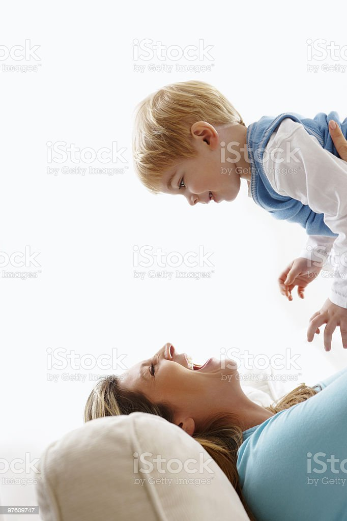 happy young mother lifting her toddler in the air royaltyfri bildbanksbilder