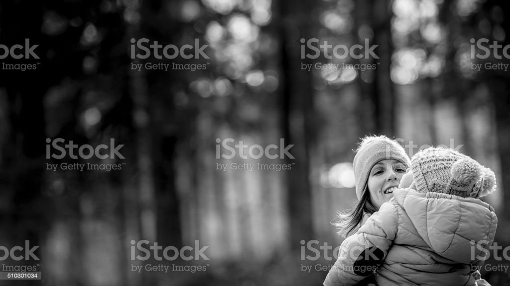 Happy young mother outside in nature holding her baby stock photo