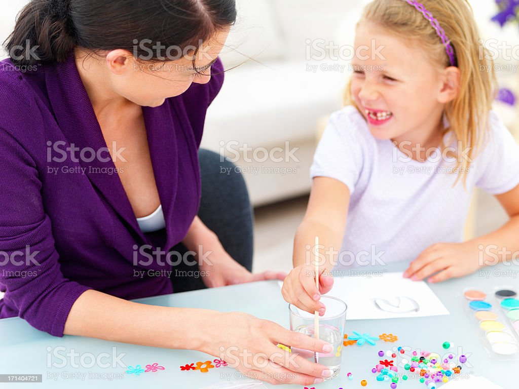 Happy young mother sitting with her daughter and drawing royalty-free stock photo