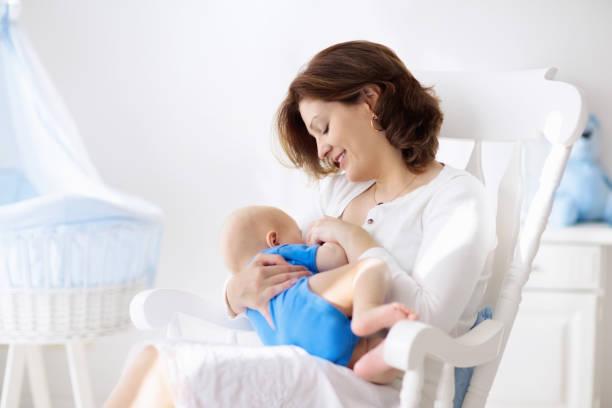 happy young mother with baby boy at home - amamentação imagens e fotografias de stock