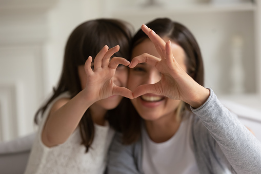 Happy young mother with cute little daughter making focused heart sign with hands, looking at camera. Smiling millennial mom and small girl showing love gesture together, expressing care, affection.