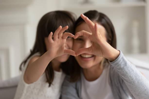 feliz joven madre con hija pequeña haciendo señal de corazón enfocado. - hija fotografías e imágenes de stock