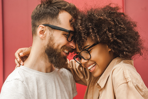 Happy Young Multicultural Couple In Eyeglasses Hugging On Street Stock Photo - Download Image Now