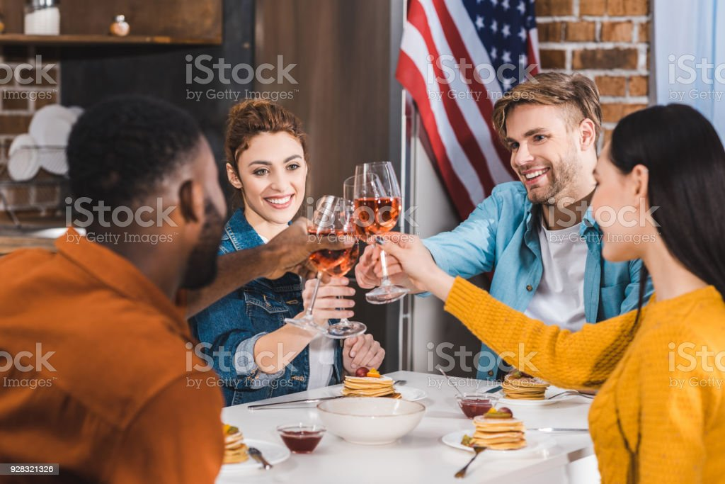 happy young multiethnic friends clinking wine glasses above table stock photo