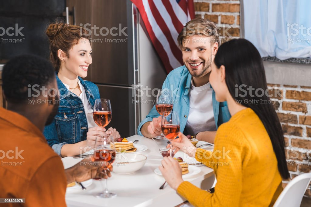 happy young multiethnic friends drinking wine and talking at table stock photo