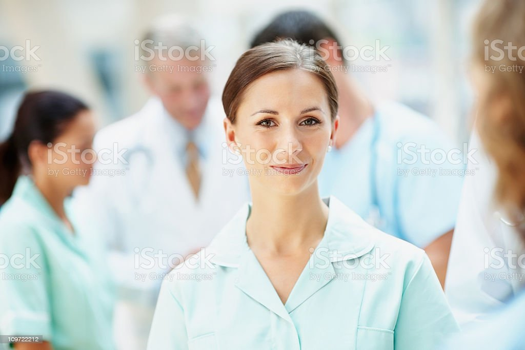 Happy young nurse with her blur medical team in background royalty-free stock photo