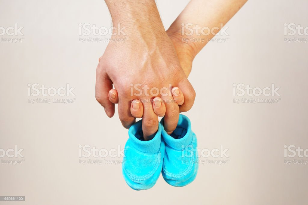 Happy young parents hold in their hands baby shoes of future child stock photo