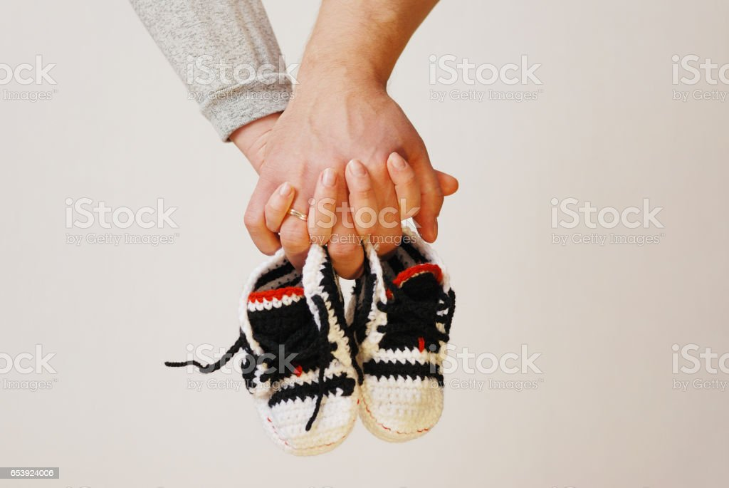 Happy young parents hold in their hands children's shoes of future child stock photo