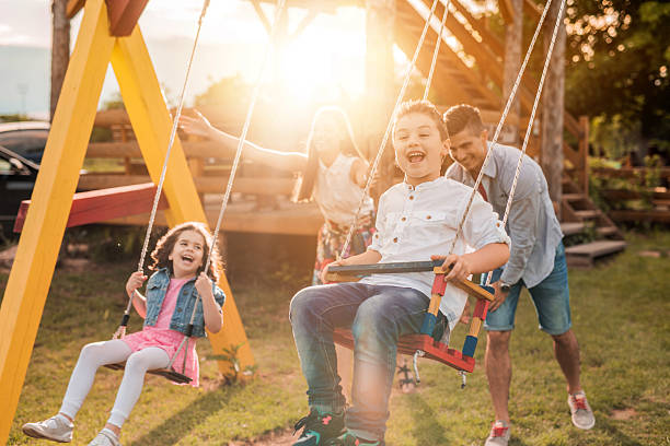 Happy young parents swinging their children at sunset. stock photo