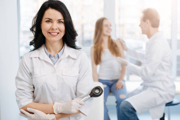 Happy young patient having conversation with dermatologist the hospital stock photo