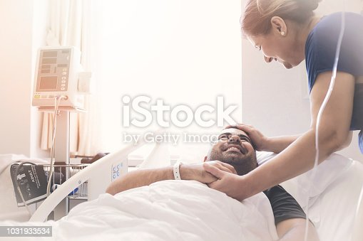 Happy young patient lying on a medical bed next to his mother