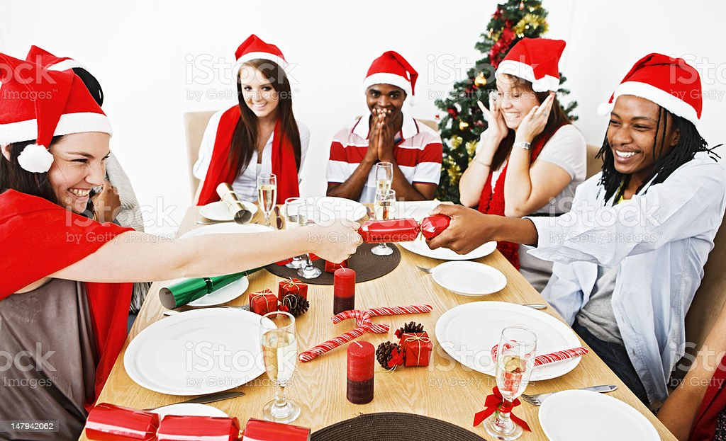 Happy young people anticipate the bang from a Christmas cracker royalty-free stock photo