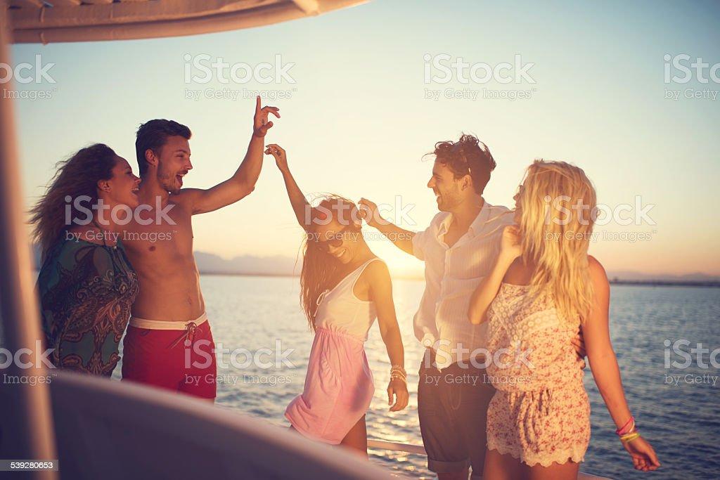 Feliz jovens dançar sobre um barco ao pôr do sol. - fotografia de stock