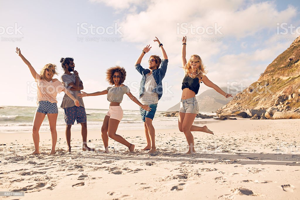 Happy young people dancing on the beach stock photo