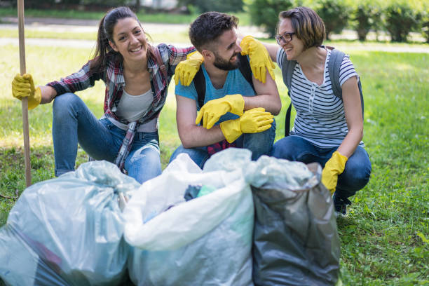 Happy young people doing community work in the local park stock photo