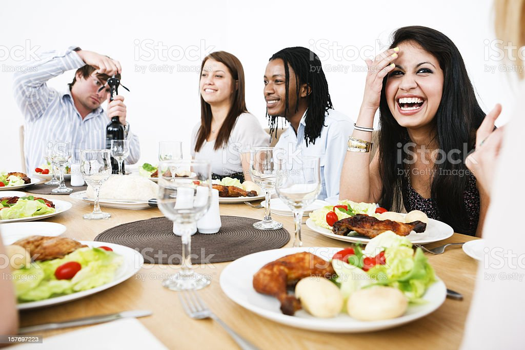 Happy young people gathered round dining table royalty-free stock photo