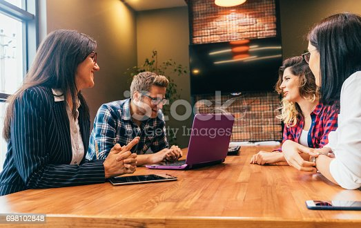 681735120istockphoto Happy young people having a business meeting 698102848