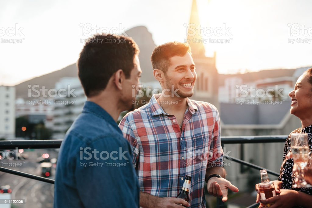 Happy young people having a rooftop party stock photo
