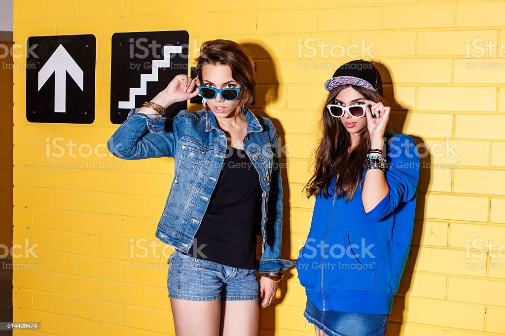 happy young people having fun in front of yellow wall stok fotoğrafı