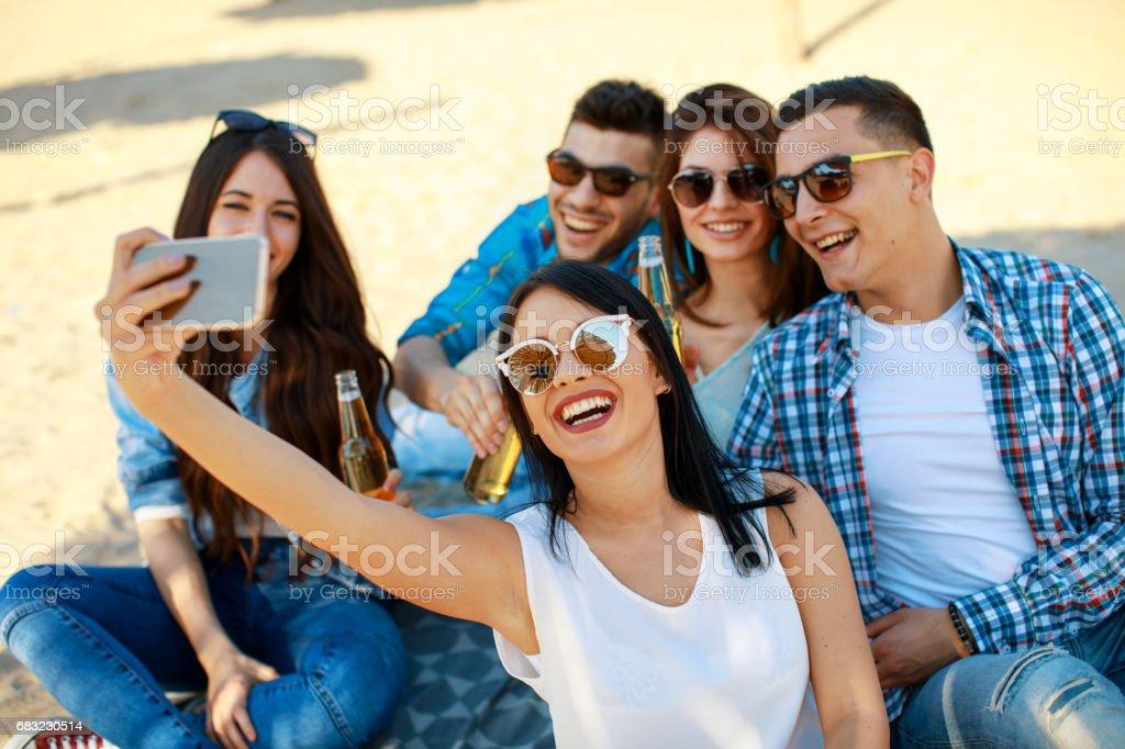 快樂的年輕人開心上海灘喝啤酒,做自拍照 免版稅 stock photo