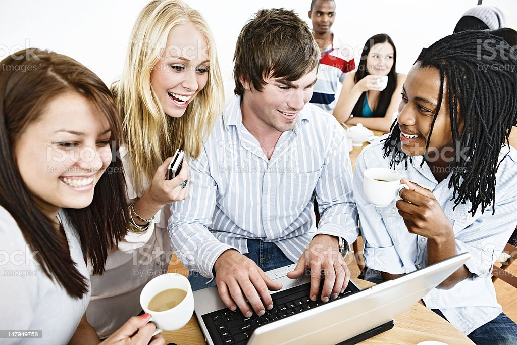Happy young people in coffee shop laugh at laptop screen royalty-free stock photo