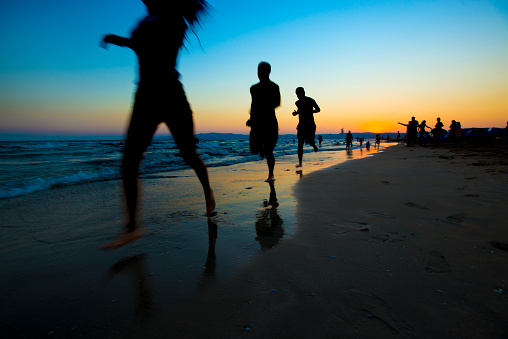 Happy Young People Is Running Of Sunset Beach Stock Photo ...