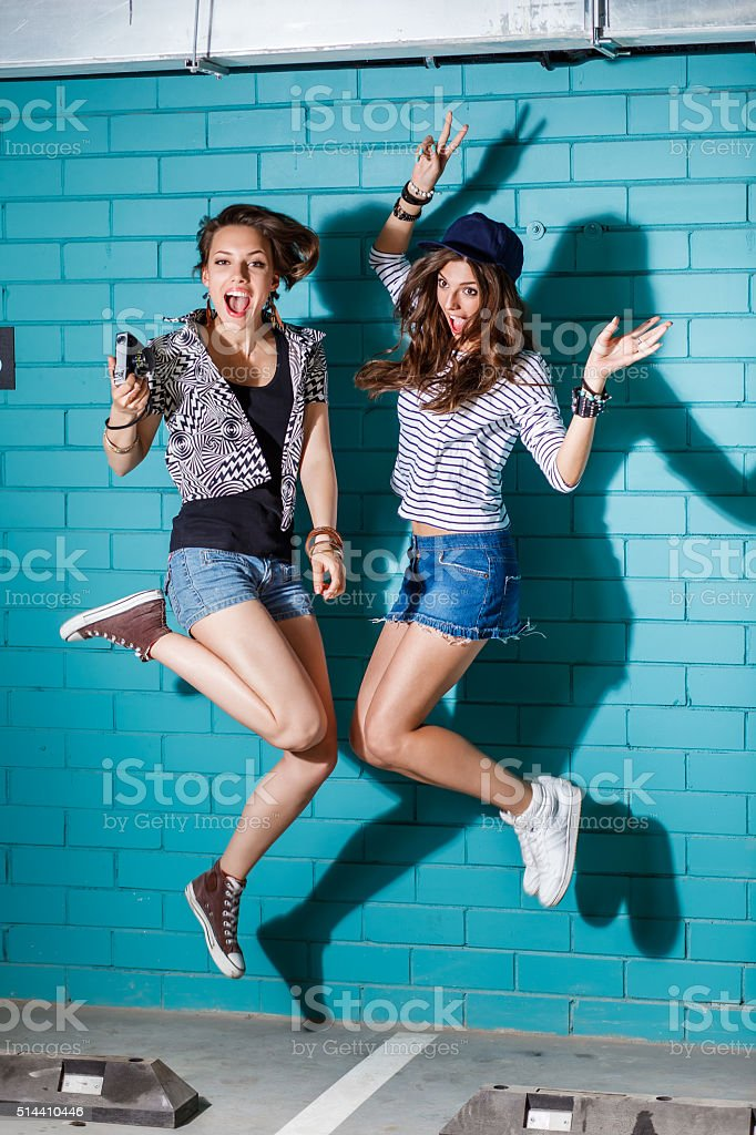 happy young people jumping in front of blue brick wall stok fotoğrafı