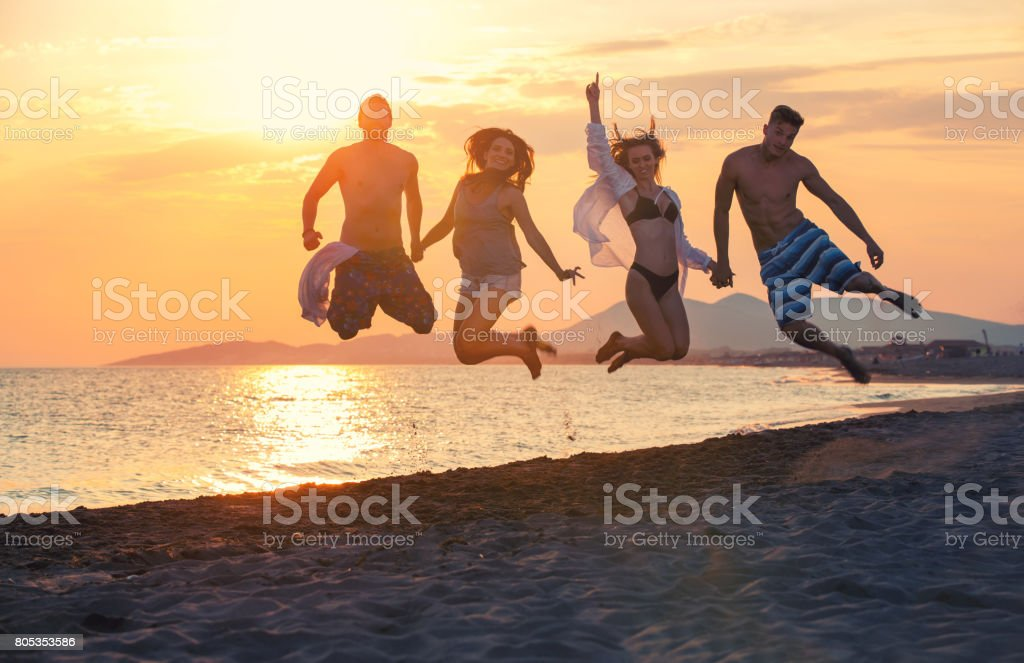 Group of happy people dancing and jumping inside sea on beautiful...