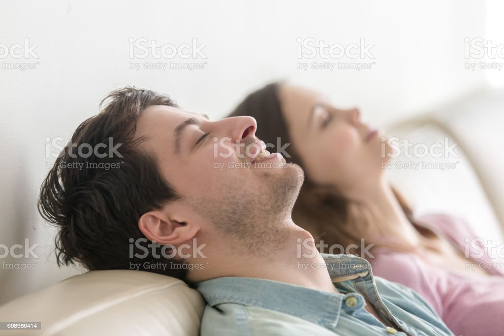 Happy young people relaxing with eyes closed indoors. Side view stock photo