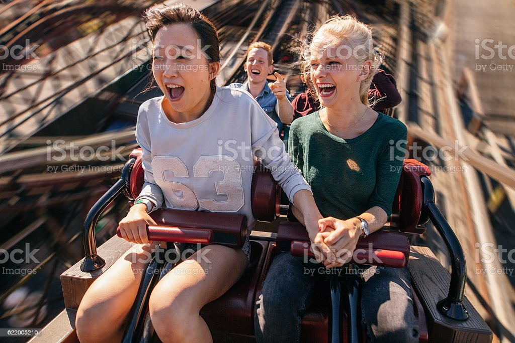 Happy young people riding a roller coaster stock photo