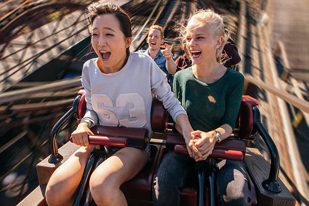 Happy young people riding a roller coaster – Foto