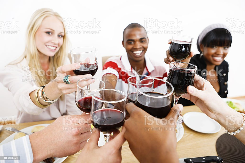 Happy young people toast in red wine at dinner table royalty-free stock photo