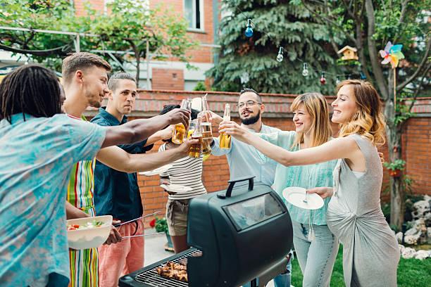 Felices jóvenes brindis en fiesta barbacoa. - foto de stock